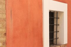 Finestra isolata con le grate in una parete arancio immagine stock