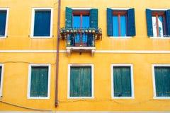Finestra italiana con la parete gialla luminosa degli otturatori di legno Immagine Stock