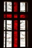 Finestra macchiata con la croce rossa in una chiesa Fotografie Stock