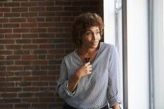 Finestra matura premurosa dell'ufficio di Looking Out Of della donna di affari immagine stock libera da diritti