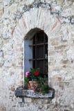 Finestra medievale con i vasi di fiori Immagine Stock