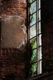 Finestra misteriosa in una vecchia costruzione di mattone con molto esterno verde Immagine Stock
