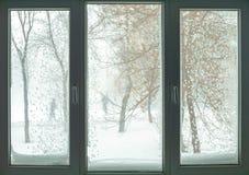 Finestra in piano russo con la bufera di neve e gli alberi della neve fotografia stock