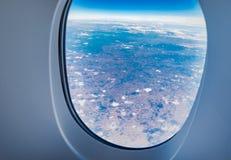 Finestra quando volano veda attraverso alla nuvola ed al cielo blu, TR dell'aeroplano fotografie stock libere da diritti