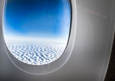 Finestra quando volano veda attraverso alla nuvola ed al cielo blu, TR dell'aeroplano immagini stock libere da diritti