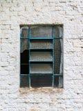 Finestra rotta blu su un muro di mattoni bianco Fotografia Stock Libera da Diritti