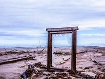 Finestra rotta su una spiaggia abbandonata che trascura il mare e la siluetta di una nave fotografie stock