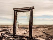 Finestra rotta su una spiaggia abbandonata che trascura il mare e la siluetta di una nave fotografia stock