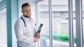 Finestra seguente stante di medico maschio amichevole grande alla cartella della tenuta del corridoio dell'ospedale in sue mani stock footage