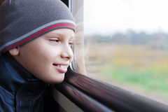 Finestra sveglia di sguardo del treno di sorriso del bambino Immagini Stock