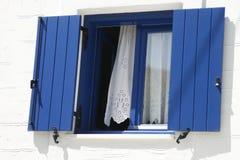 Finestra tradizionale con gli otturatori blu in Grecia Immagine Stock