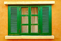 Finestra verde sulla parete gialla Immagini Stock