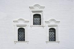 Finestre antiche sulla parete bianca Fotografia Stock Libera da Diritti