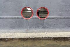 Finestre circolari rosse sulla nave da crociera nera Fotografia Stock Libera da Diritti