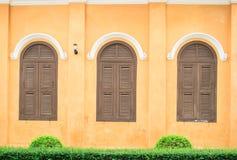 Finestre d'annata con la vecchia parete gialla fotografie stock libere da diritti