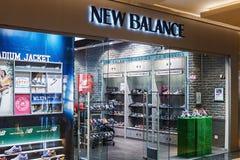 Finestre del negozio di New Balance in un centro commerciale Immagine Stock