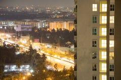 Finestre dell'appartamento alla notte con il paesaggio urbano asiatico di Bangkok nei precedenti Il traffico e l'impulso prospero Fotografia Stock Libera da Diritti