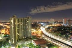 Finestre dell'appartamento alla notte vicino al sistema di strada principale moderno con traffico pesante Il distretto aziendale  Immagine Stock