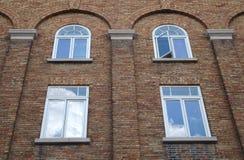 Finestre dell'arco del muro di mattoni che sviluppano vecchia architettura della facciata Fotografia Stock