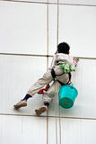 Finestre di pulizia dell'uomo su un'alta costruzione di aumento Immagine Stock Libera da Diritti