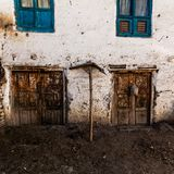 Finestre e porte di legno sporche tradizionali antiquate in piccolo paesino di montagna nel Nepal fotografia stock