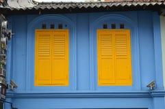 Finestre ed otturatori coloniali gialli e blu in poca India, Singapore Immagine Stock Libera da Diritti