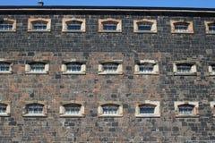 Finestre escluse sulla parete della prigione Fotografia Stock Libera da Diritti
