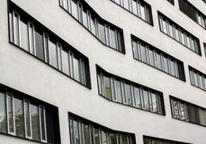 Finestre moderne in una fila su una costruzione curva Struttura di urbanizzazione architettonica Fotografia della via nello stile fotografia stock