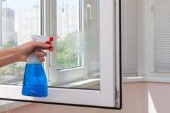 Finestre pulite del PVC della plastica di Houseworker con il detersivo immagine stock libera da diritti