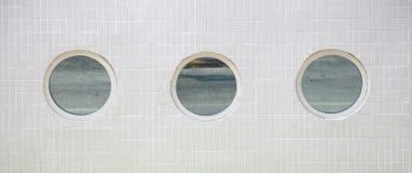 3 finestre rotonde in una parete piastrellata bianca Fotografie Stock