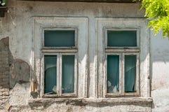 Finestre rotte di vecchia casa abbandonata con il gesso della sbucciatura e nocivo Fotografia Stock