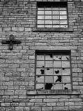 Finestre rotte in una vecchia costruzione vandalizzata abbandonata vuota Fotografia Stock