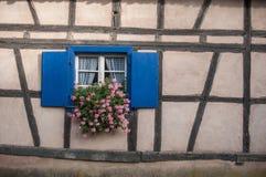 Finestre storiche con i gerani in villaggio alsaziano Fotografia Stock