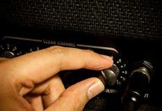Finger adjust volume of amplifier. Stock Photos