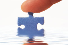 Finger And Puzzle In Water Royalty Free Stock Image