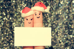 Finger art of couple celebrates Christmas. Concept of man and woman laughing in new year hats. Happy pair showing white blank page. Toned image Stock Photo