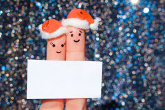 Finger art of couple celebrates Christmas. Concept of man and woman laughing in new year hats. Happy pair showing white blank page. Toned image Royalty Free Stock Image