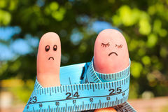 Finger art of couple with meter. concept man is thin, woman is fat. Royalty Free Stock Images