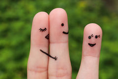 Finger art of a couple. Woman hugs and kisses the man, and he's flirting with another woman. Royalty Free Stock Images