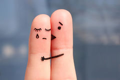 Finger art of displeased couple. Woman cries, man reassures her. He kisses and hugs her Royalty Free Stock Images