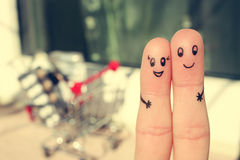 Finger art of a Happy couple. A man and a woman hug on the background shopping cart. Royalty Free Stock Photography