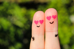 Finger art of a Happy couple. A man and a woman hug with pink hearts in the eyes. Stock Photos