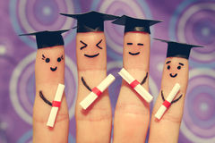 Finger art of students. Graduates holding their diploma after graduation. Toned image Stock Images