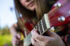 Finger auf der Schnurnahaufnahme, junges Mädchen spielt auf der Akustikgitarre liebhaberei Stockbild
