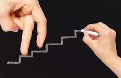 Finger auf Kreidetreppe steigen während Hand mit Kreide Lizenzfreies Stockfoto