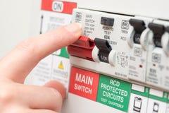 Finger auf MAIN Schalter auf RCD-Leistungsschalter-Brett Lizenzfreies Stockbild