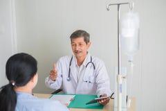 Finger aumentado doctor asi?tico mayor y mirada en el paciente femenino con sonrisa imagen de archivo libre de regalías