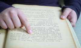 finger av en flicka på en bok arkivbild