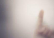Finger bak det frostade exponeringsglaset Royaltyfri Bild