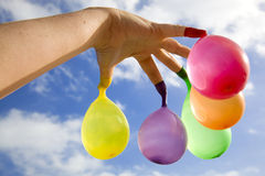 Finger balloons. Open hand with multicolored water filled balloons hanging from the fingers, with a cloudy blue sky as background Stock Photo